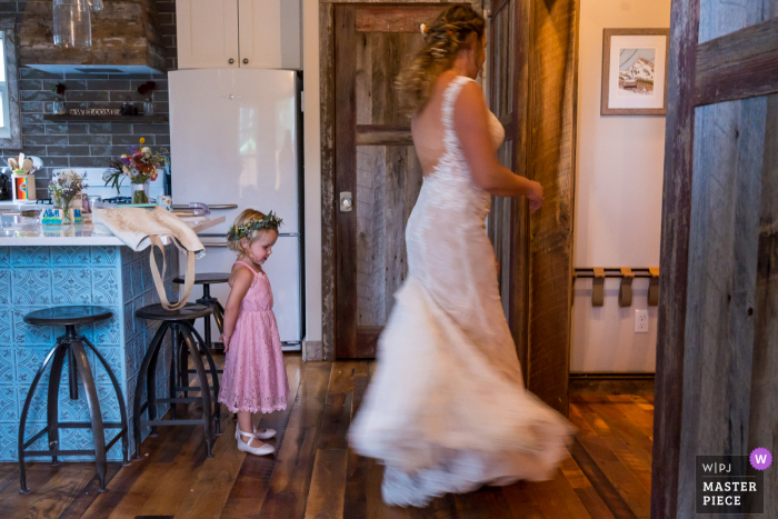 Colorado marriage preparation time award-winning picture capturing bride showing the flower girl the dress. The world's best wedding image competitions are held by the WPJA