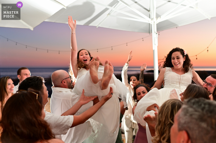 Leblon São João, Costa da Caparica, Lisbon outdoor marriage reception party award-winning photo that has recorded Guests throwing the couple in the air. The world's top wedding photographers compete at the WPJA