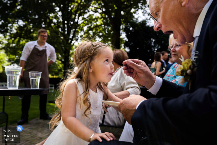 De Landgoederij in Bunnik outdoor marriage reception party award-winning photo that has recorded the flower girl getting cake from her grandfather. The world's top wedding photographers compete at the WPJA