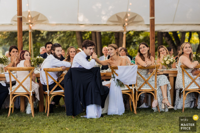 Woodstock, Vermont marriage reception party award-winning photo that has recorded The groom reacting under the tent during his best mans toast - from the world's best wedding photography competitions offered by the WPJA