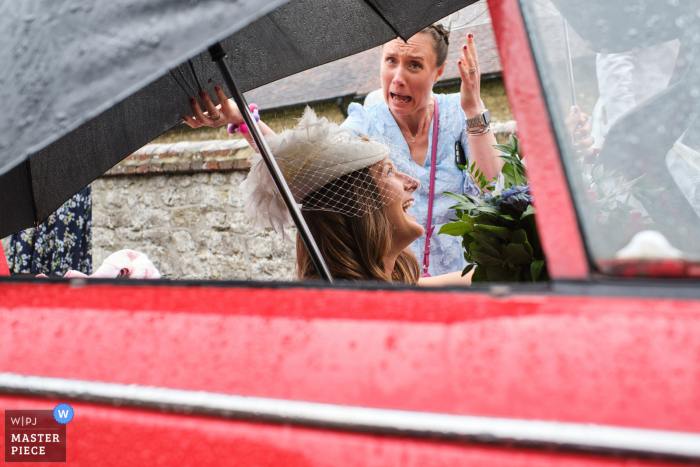 St. Dunstan's Church, West Peckham, Kent nuptial day award-winning image of The bride and one of her bridal party share a funny moment during the couple's rain soaked departure in their open top vintage sports car