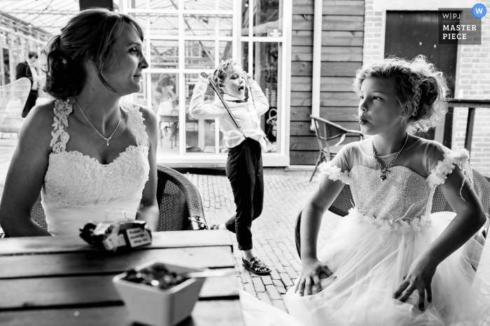 Noord Brabant marriage reception party award-winning photo that has recorded kids and the bride in black and white - from the world's best wedding photography competitions offered by the WPJA