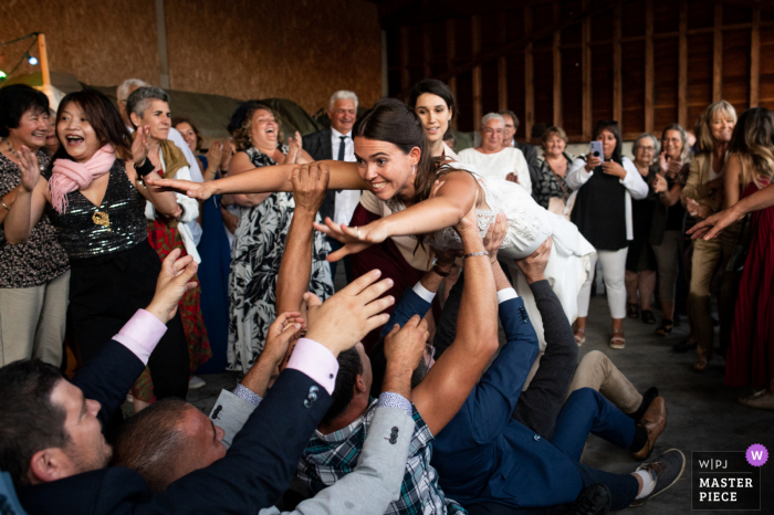 Domaine Pierre Gaillard marriage reception party award-winning photo that has recorded a Paquito, when the Bride jumps on people - from the world's best wedding photography competitions offered by the WPJA