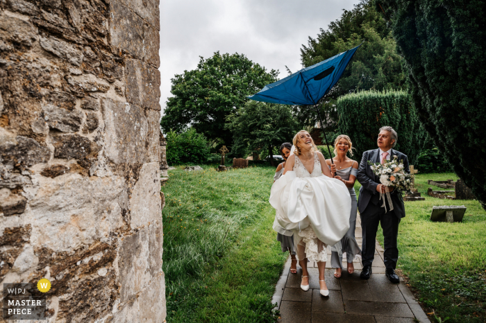 Somerset, England nuptial day award-winning image of The bridal party arriving at the church in the rain as the wind blows their umbrella inside out - from the world's best wedding photography competitions hosted by the WPJA