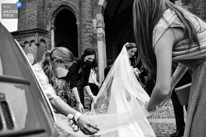 Chiaravalle della Colomba, Castell' Arquato marriage ceremony award-winning image showing The arrangement of the brides veil before entering the church - from the world's best wedding photography competitions presented by the WPJA