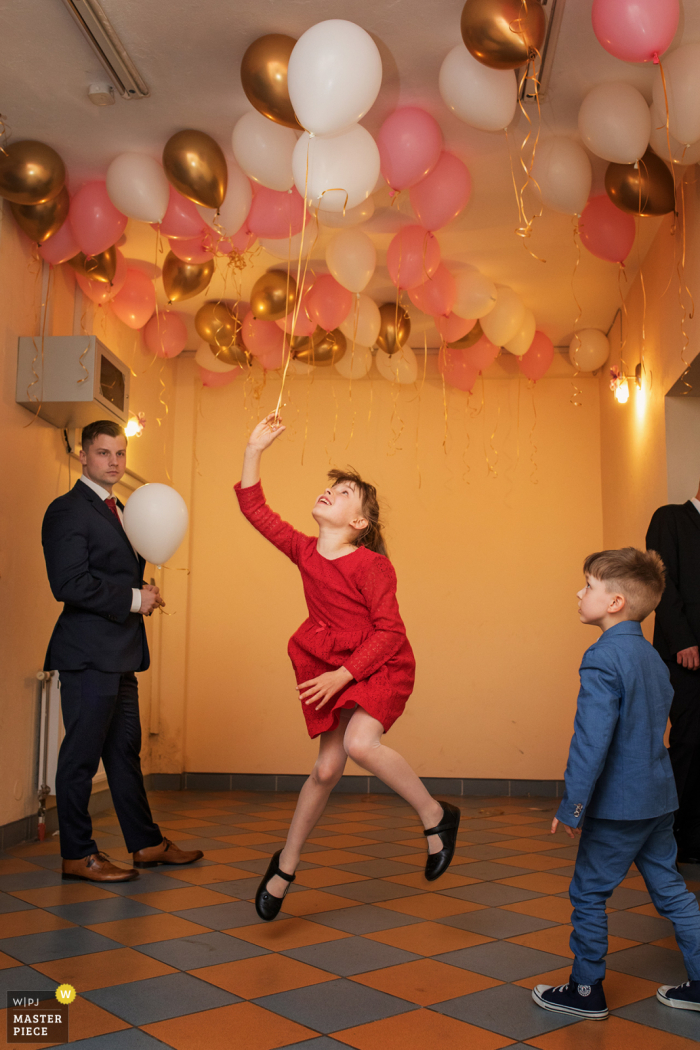 Krakow marriage reception party award-winning photo that has recorded a girl jumping for a balloon - from the world's best wedding photography competitions offered by the WPJA