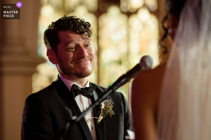 St. Jax Church, Montreal marriage ceremony award-winning image showing An emotional groom listening to his bride reading her vows - from the world's best wedding photography competitions presented by the WPJA