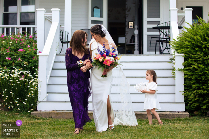 Dockside Guest Quarter, York, Maine nuptial day award-winning image of The bride and her mother photobombed by the flower girl as they come down the aisle on the wedding day - from the world's best wedding photography competitions hosted by the WPJA