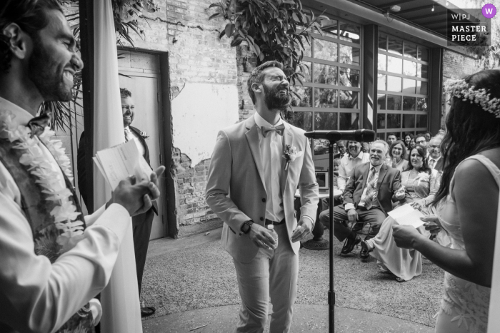 Millwick, Los Angeles marriage ceremony award-winning image showing The groom laughs hard while his bride reads her vows - from the world's best wedding photography competitions presented by the WPJA
