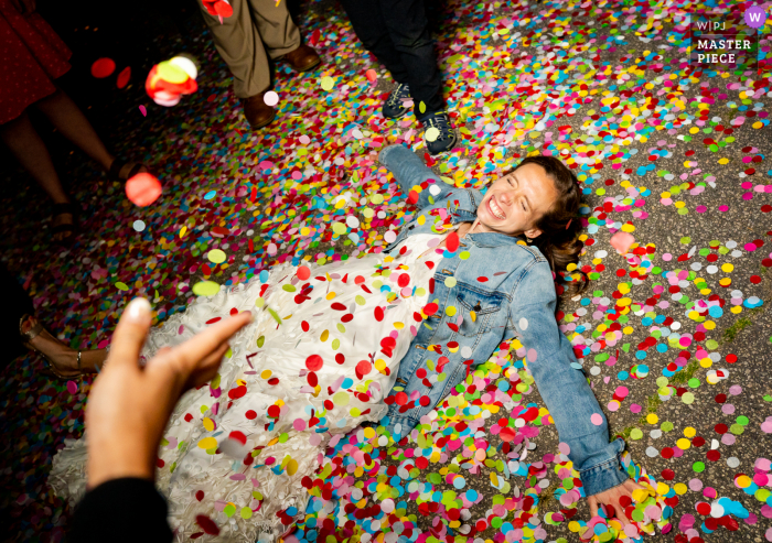Wake Forest, North Carolina marriage reception party award-winning photo that has recorded The bride makes angels in confetti after their special exit - from the world's best wedding photography competitions offered by the WPJA