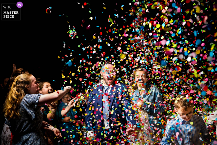 Wake Forest, NC marriage ceremony award-winning image showing Bride and groom walking through confetti as part of their special exit - from the world's best wedding photography competitions presented by the WPJA