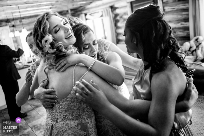 Pagosa Springs, CO nuptial day award-winning image of Bride hugging her bridesmaids on her wedding day - from the world's best wedding photography competitions hosted by the WPJA