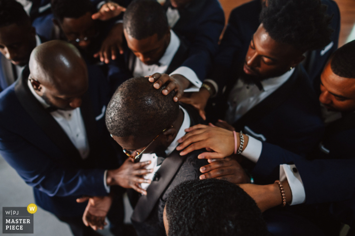 Heritage Fellowship Church, Virginia getting ready for marriage award-winning picture capturing The groom (who is also a minister) is being blessed by the groomsmen - from the world's best wedding photography competitions held by the WPJA