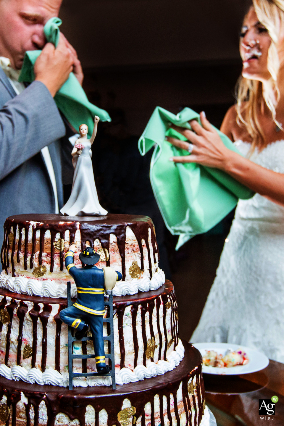 Rock Island Lake Club New Jersey wedding venue photo detail of the fireman cake cutting with the bride and groom wiping cake off their faces