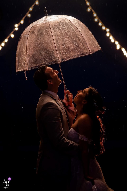 斯克里普斯海滨论坛-拉荷亚加州。 雨来了,新娘和新郎共用一把雨伞。