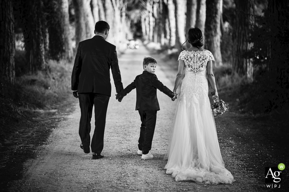 Castello di Rosciano retrato de boda en blanco y negro de la novia, el novio y el niño caminando por el sendero arbolado