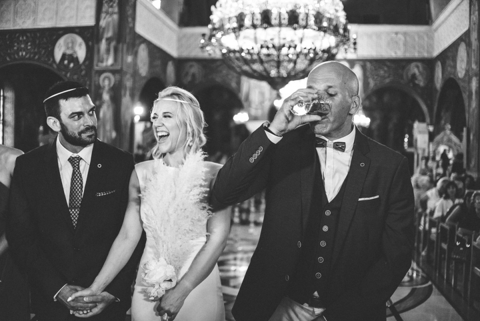 Photo of groomsmen drinking wine during the wedding ceremony in Varobopi, Greece