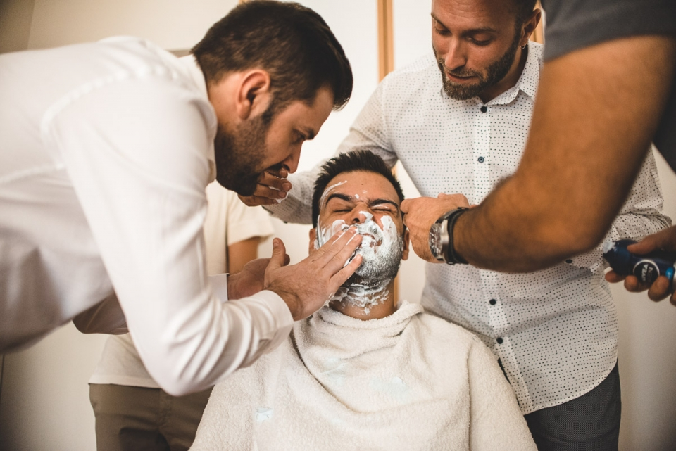 Wedding photo of friends shaving the groom in Athens, Greece