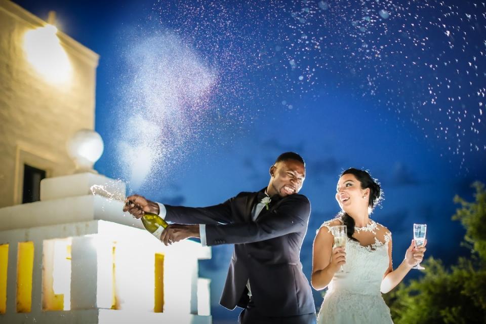 El fotógrafo de bodas Monopoli captura el rocío de champaign del novio con su novia a su lado