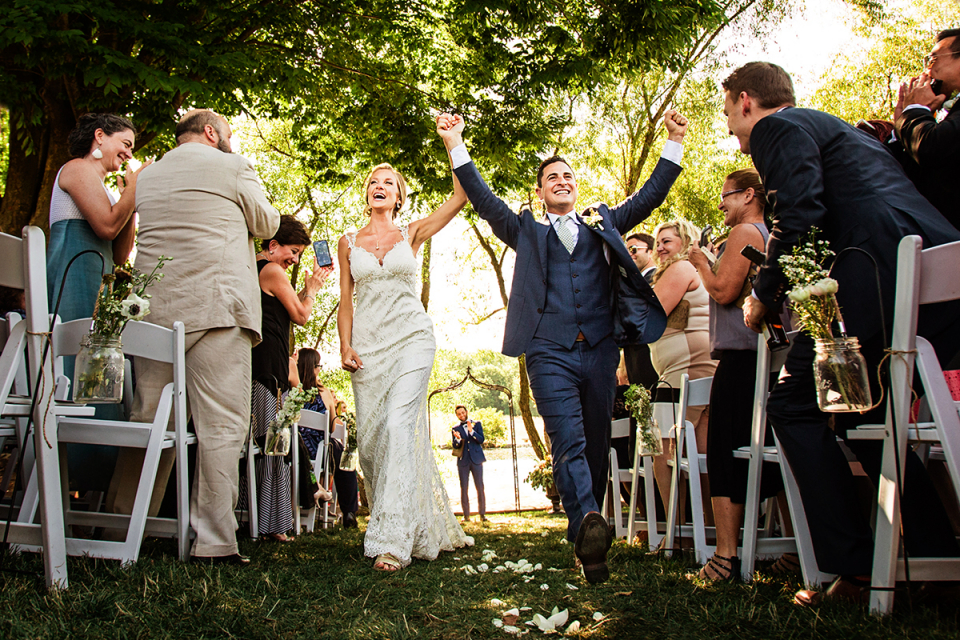 Bride and Groom exit the ceremony happily holding hands outside The Farm at Eagles Ridge, Lancaster PA
