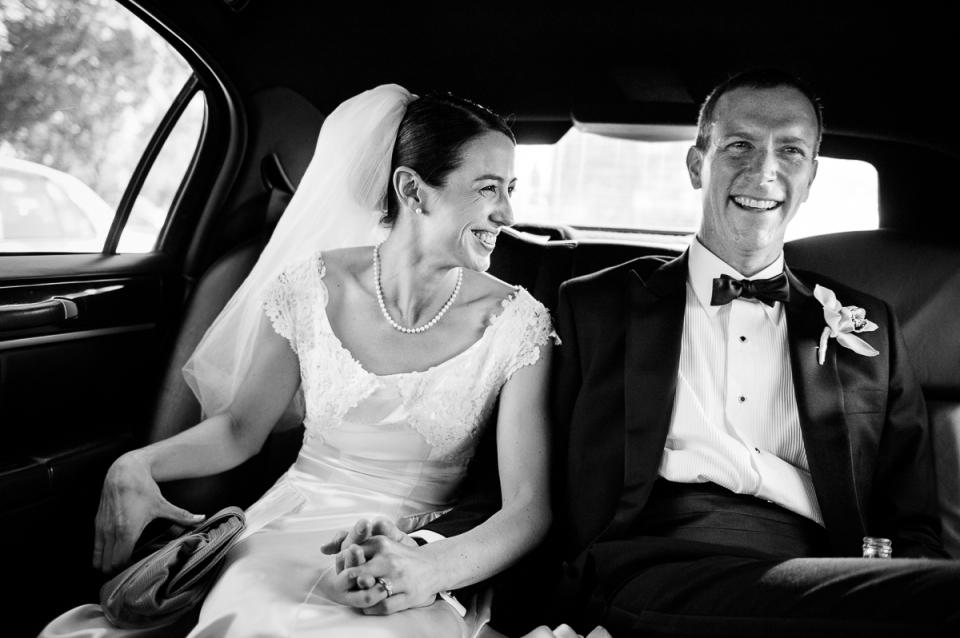 Novia y novio en limusina en ruta a la boda de Glenview Mansion en Rockville, Maryland.
