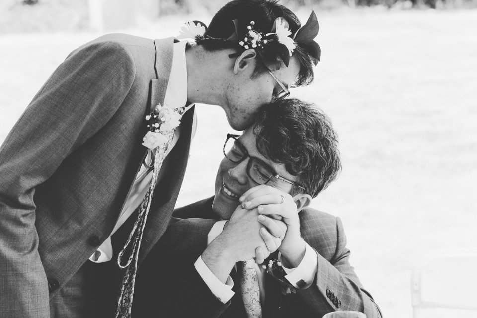 Black and white image of groom kissing the head of his husband