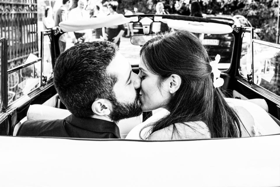 Scardavilla, Meldola, Forlì-cesena, Italie photo de mariage des mariés s'embrassant à l'arrière d'une voiture décapotable.