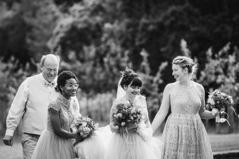 The bride is walking along with some help at Black Pig Orchard, Chelwood Gate, East Sussex, United Kingdom