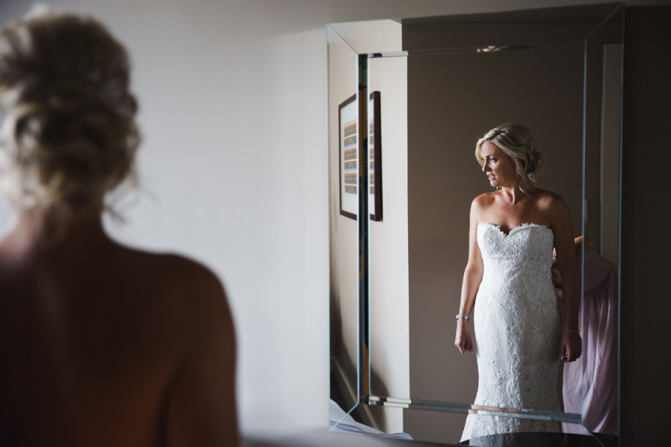 Photo of the bride standing before a mirror at the St George's Hill Golf Club, Weybridge, United Kingdom