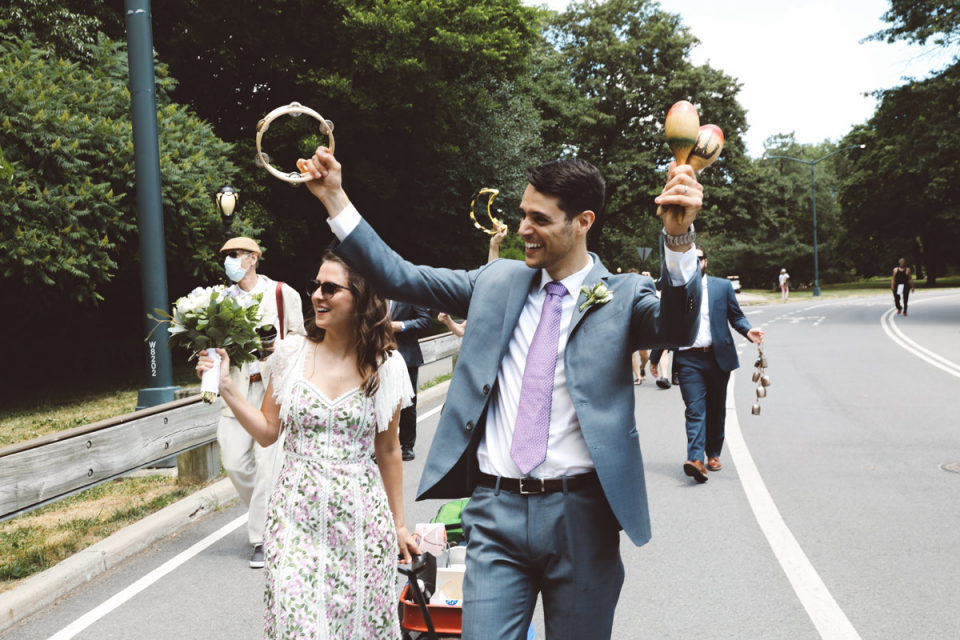 Central Park Elopement image of the bride and groom walking in the street