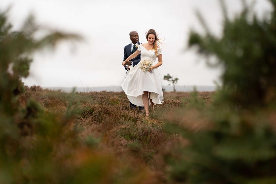 Bride & groom walking through heather - Poole, Dorset wedding photography