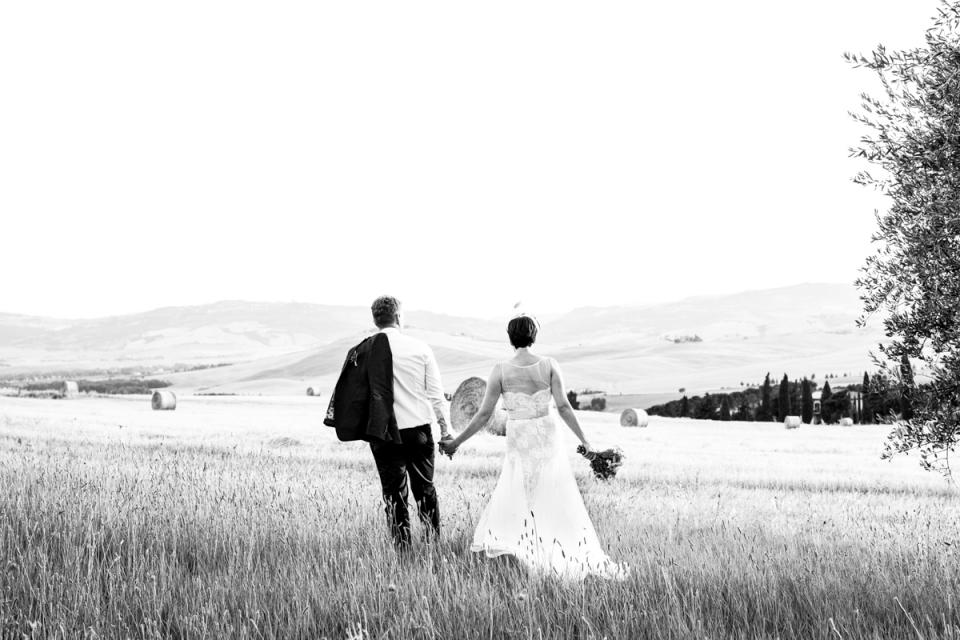 Place principale de Monticchiello, Toscane - image de mariage bw du couple marchant dans les champs