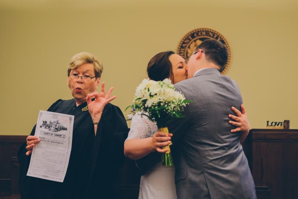 Foto van paar kussen naast officiant huwelijk tijdens hun ceremonie