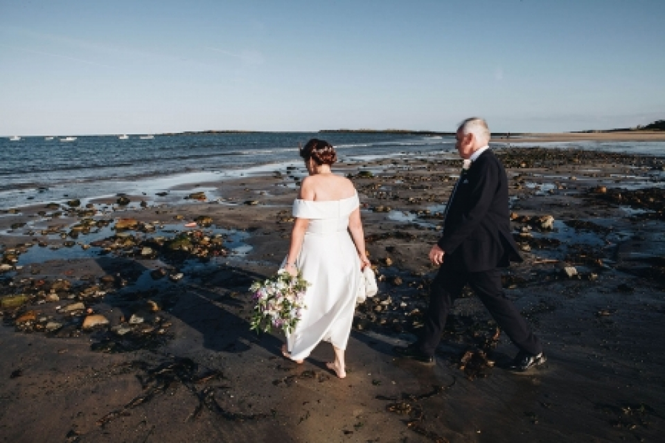 The Ship Inn, Low Newton | Wedding Photography showing the Bride and Groom walking to the beach