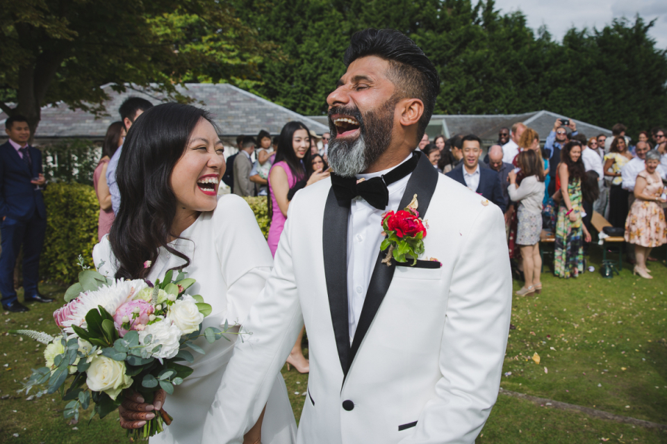 Wedding photo of the bride and groom laughing after their outdoor ceremony at High House, Fillongley Warwickshire, United Kingdom