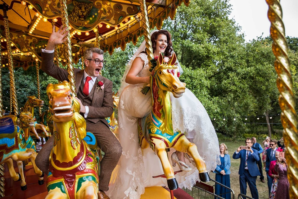 De bruid en de bruidegom rijden carrouselpaarden huwelijksfotografie in het West Green House, Hampshire, Verenigd Koninkrijk