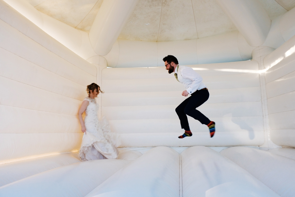 Bride and groom playing on a bouncy castle at Bordesley Park Farm by documentary wedding photographer Birmingham Clive Blair Photography