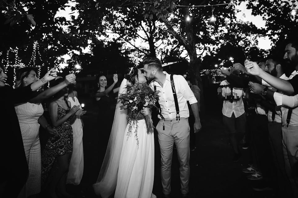 Tekirdag, Turquie photo de la mariée et du marié s'embrassant sous les arbres entourée d'invités.