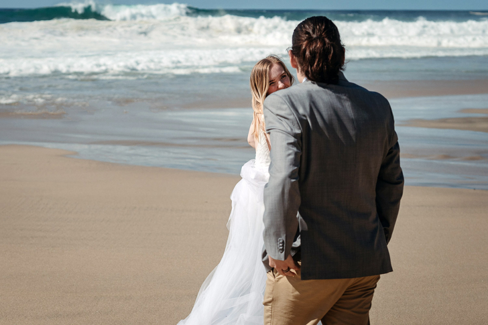 Big Sur elopement image of the California bride and groom having fun at the beach