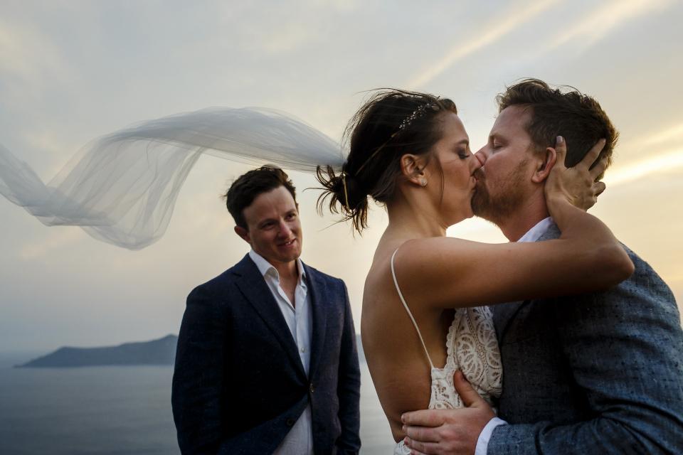Fira, Santorini, Greece wedding kiss photography from the ceremony by Ufuk Sarisen