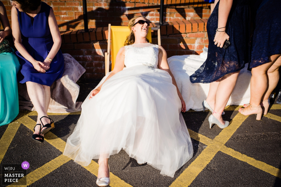 Bride sits down in her dress at the wedding at the Silverdale Village Hall