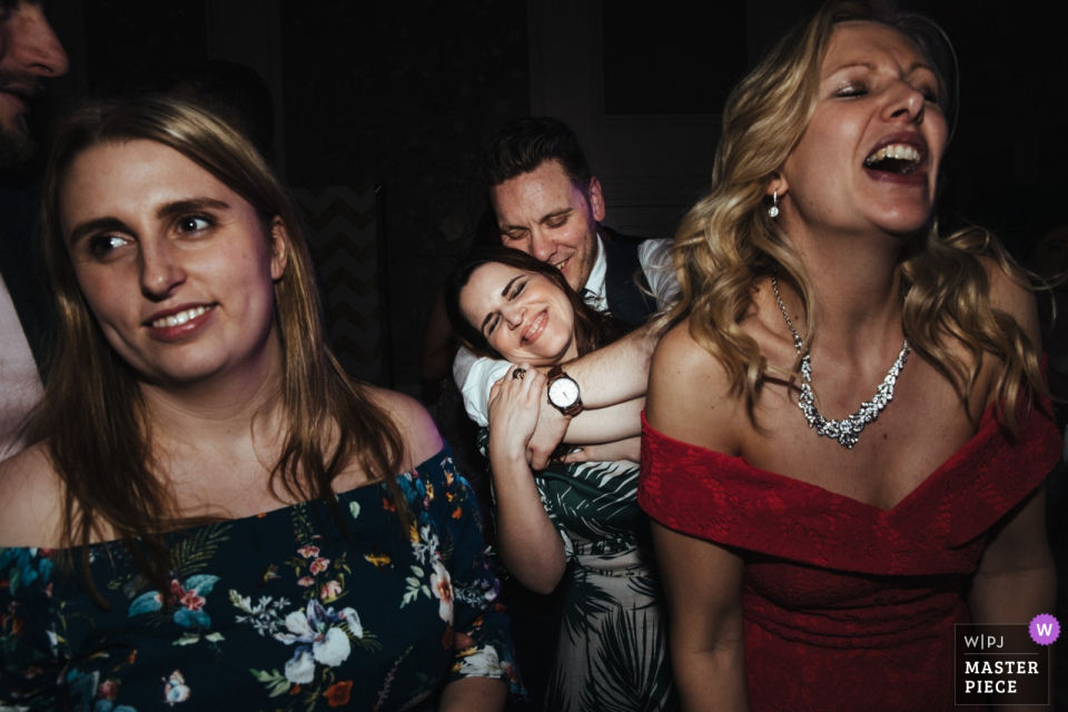 Bridal party singing and smiling at the wedding reception at The George in Rye, UK