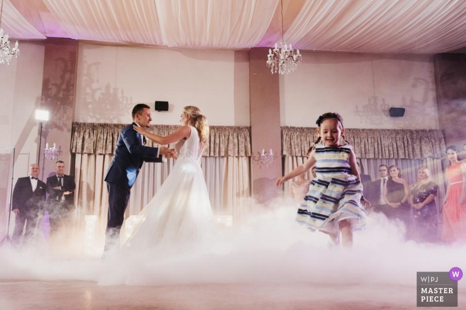 Kleines Mädchen läuft herum, während die Braut und der Bräutigam am Hochzeitsempfang JF Duet, Goleniów, Polen tanzen