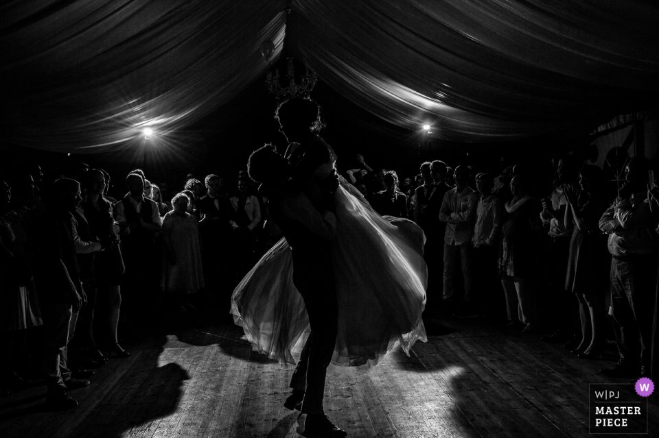 Groom lifts the bride while dancing at the wedding reception in Châtreau de Kerambleiz