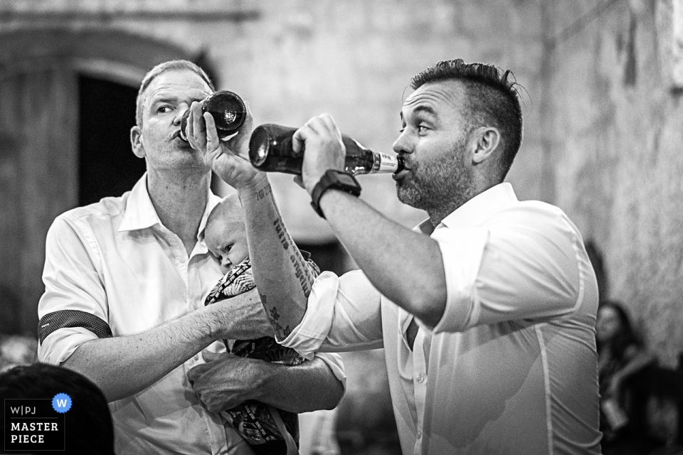 Groom and best man enjoy drinks while holding a baby in albergo la badia - Orvieto