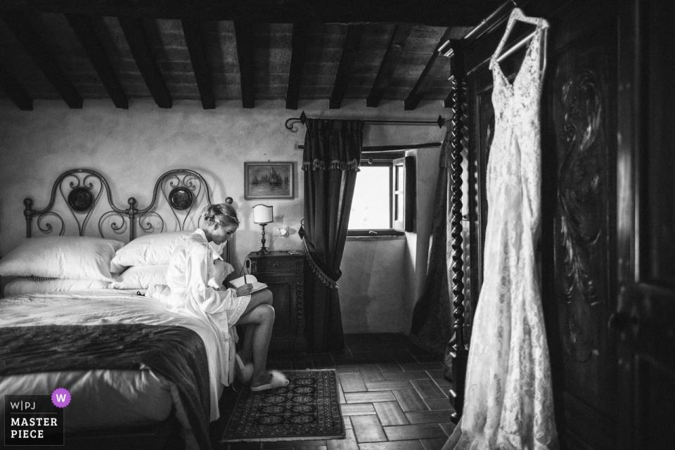 Abbazia San Faustino foto de la boda de la novia escribiendo una nota en la cama mientras su vestido cuelga cerca.