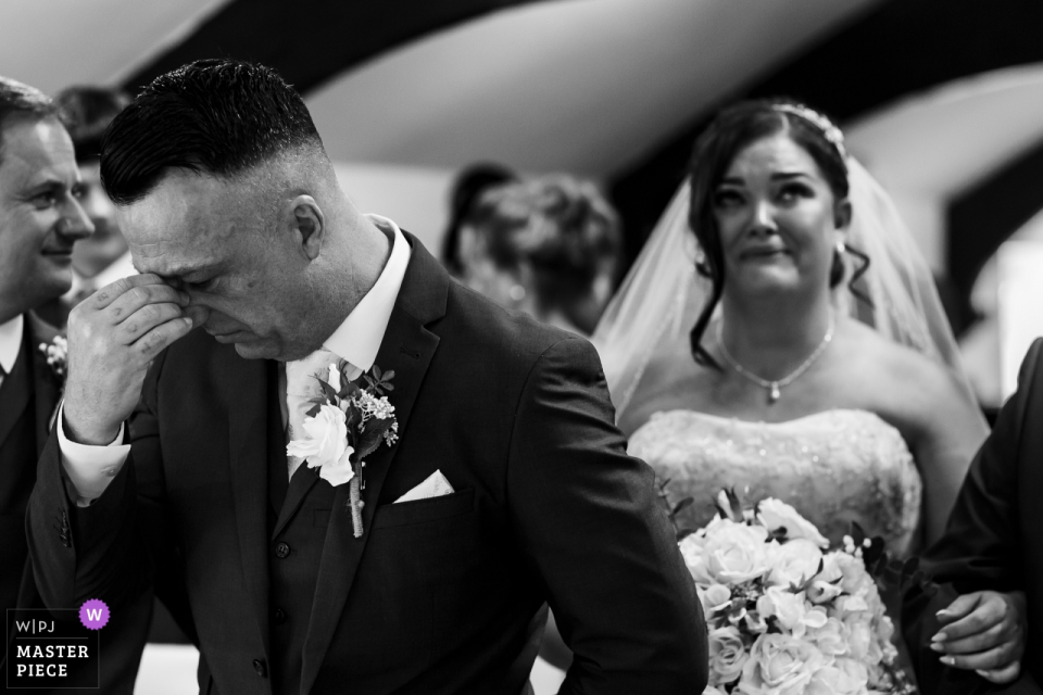 The groom holds his hand to his face as the bride walks down the aisle at The Joshua Bradley in this black and white photo by a Lancashire, England wedding reportage photographer.
