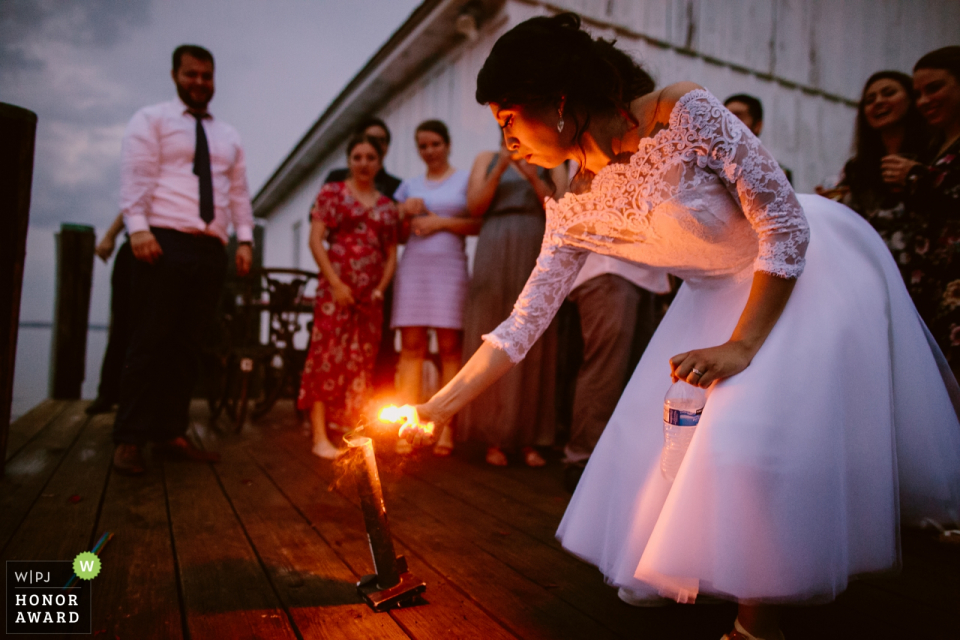 Bride lights a candle at her wedding ceremony at Hope House in Easton, MD