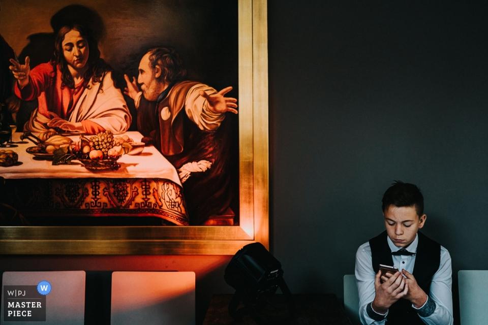 Documentaire de mariage de Gasthaus zur Linde, photo du petit garçon jouant au téléphone près d'œuvres d'art - mariages en Allemagne