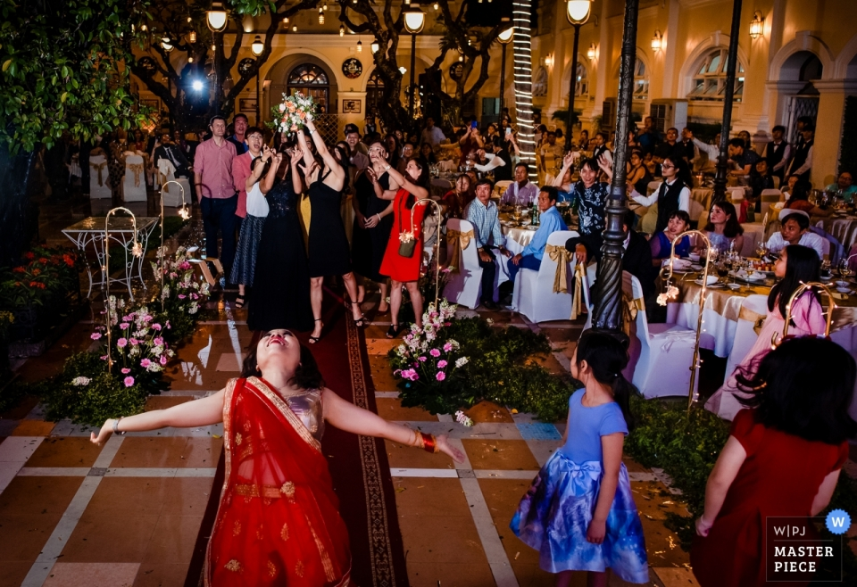 Bride tosses bouquet to guests at the Hotel Sai Gon Continental, Ho Chi Minh city, Viet Nam